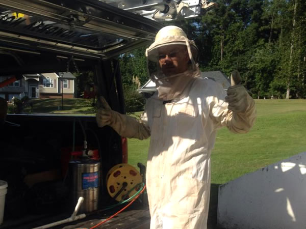 Man in a bee suit giving two thumbs up signs at a bee removal job in Buckhead, Georgia